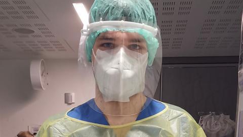 Pfleger Alexander Riedel mit Schutzausrüstung an seinem Arbeitsplatz