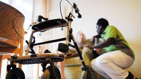 Pflegekraft spricht mit Seniorin