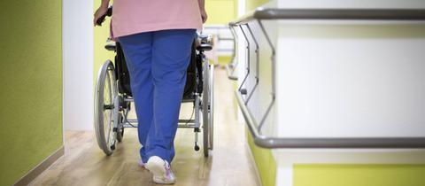 Pflegerin schiebt Heimbewohner im Rollstuhl