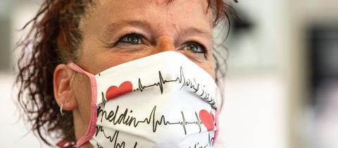 """Eine Altenpflegerin trägt einen Mundschutz mit der Aufschrift """"Krisenheldin"""""""
