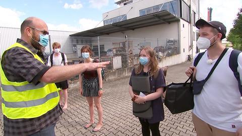 Ein älterer Mann mit gelber Warnweste gestikuliert mit ausgestreckter Hand und spricht zu vier jungen Menschen, die mit Gepäck und Absatnd vor ihm stehen.