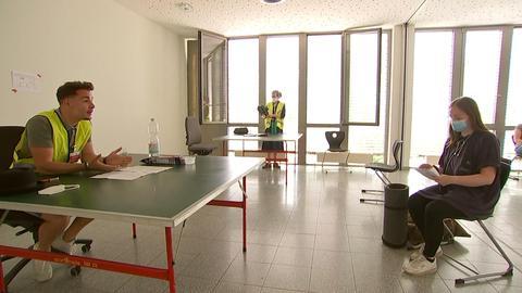 Ein junger Mann sitzt an einem Schreibtisch und ist im Gespräch mit einer jungen Frau, die mit Abstand vor seinem Tisch sitzt. Er trägt eine gelbe Warnweste. Sie hält Papiere in den Händen, neben ihr auf dem Boden eine Isomatte und ein Rucksack.