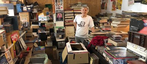 Ein Mann steht hinter Stapel voller Schallplatten