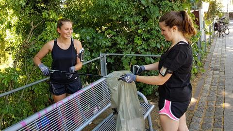 Joggerinnen sammeln Müll auf
