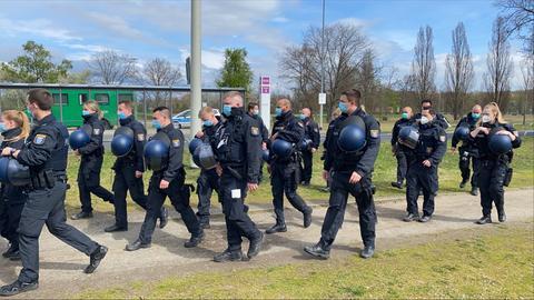 Eine Polizeigruppe läuft über das Frankfurter Rebstockgelände.