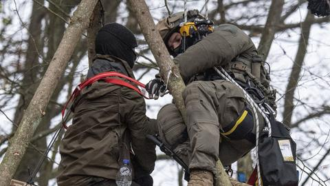 Polizist holt einen Waldbesetzer bei einer Höhenrettung von einem Baum