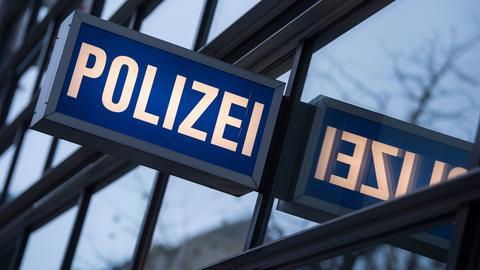 Fotografie eines Polizeiwacheschildes, welches sich in der Glasfassade spiegelt.