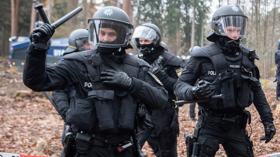 Polizisten heben ihre Schlagstöcke im Dannenröder Forst.