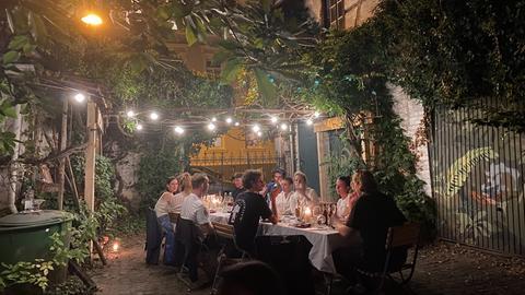 Menschen sitzen in einem Innenhof an einem langen Tisch.