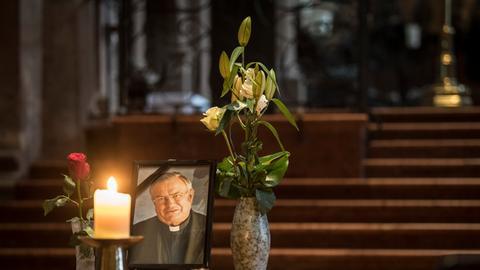Ein Kondolenzbuch, Blumen und ein Porträtfoto des verstorbenen früheren Mainzer Bischofs Kardinal Karl Lehmann stehen im Altarbereich des Mainzer Doms.