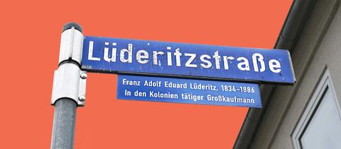 """Foto der Straßenbeschilderung """"Lüderitzstraße"""". Der Himmel hinter bzw. über dem Schild wurde durch eine terrafarbene Fläche ersetzt."""