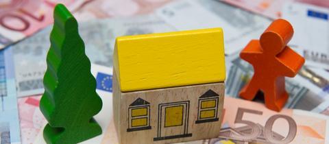 Auf Geldscheinen steht ein Spielzeughaus