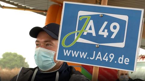 """Ein Demonstrant hält ein Schild mit dem Slogan """"Ja 49"""" hoch."""