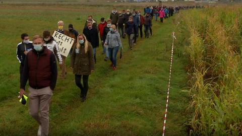 Befürworter der A49 laufen im Demonstrationszug über ein Feld.