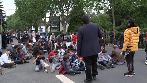 Mehrere demonstrierende Kinder und Erwachsene blockieren eine Straße