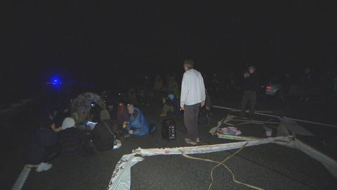 Aktivisten sitzen im Dunkeln auf der B62.
