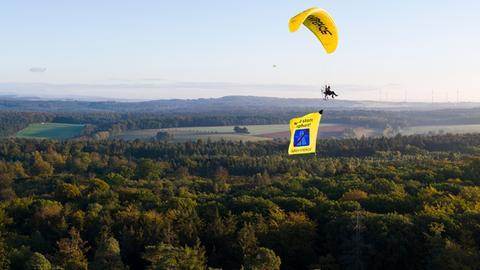 Greenpeace-Aktivist fliegt mit Gleitschirm über den Dannenröder Forst