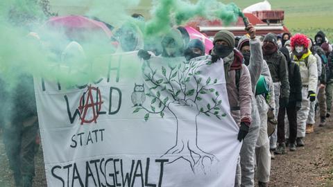 Umweltaktivisten protestieren im Dannenröder Forst mit einem Transparent und einer Rauchfackel gegen den A49-Ausbau