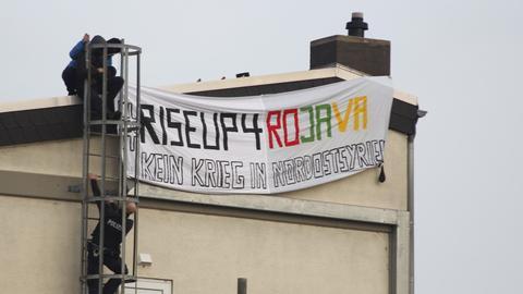 Prokurdische Aktivisten hissen ein Plakat auf dem Werksgelände.