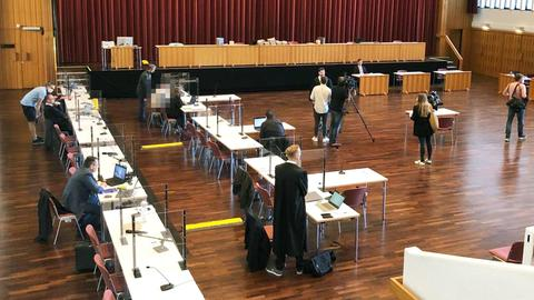 Provisorisch eingerichteter Gerichtssaal in eine Halle. Diverse Medienvertreter, Anwälte und einer der Ankgeklagte (verpixelt) sind zu sehen.