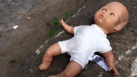 Eeine schmutzige Puppe mit geschlossenen Augen liegt auf dem Boden