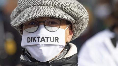 """""""Querdenken""""-Sympathisantin mit der Aufschrift """"Diktatur"""" auf der Maske"""