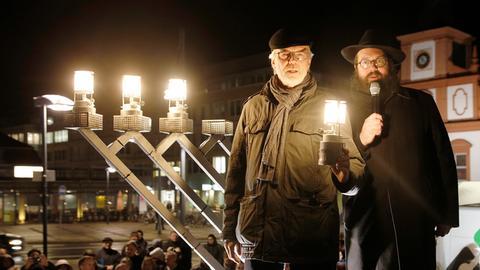 Offenbachs damaliger OB Horst Schneider (l), und Rabbiner Mendel Gurewitz entzünden am 14.12.2017 die ersten Lichter des Chanukka-Leuchters am Rathaus von Offenbach