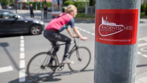 Ein Aufkleber der Initiative Radentscheid klebt an einem Ampelmast in Frankfurt.