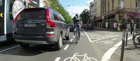 Ein SUV überholt einen Radfahrer mit extrem geringem Seitenabstand.