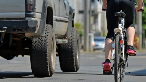 Ein Radfahrer wird von einem Geländewagen überholt.