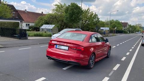 Ein rotes Auto fährt auf einem Radstreifen