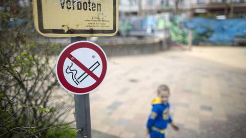 Ein Schild, welches das Rauchen verbietet hängt an einer Stange und ist im Foto im Fokus. Dahinter ein kleiner Junge und ein Spielplatz leicht unscharf.