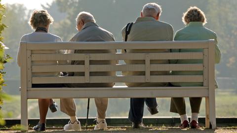 Vier Rentner sitzen auf einer Parkbank.