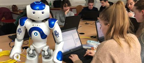 Ein weißer Roboter steht auf einem Tisch inmitten einer Schülergruppe