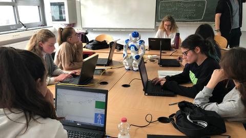 Schülerinnen arbeiten an Laptops
