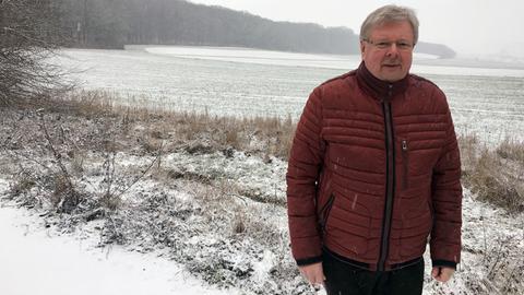 Horst Röhrig, im Hintergrund das betroffene Waldstück.