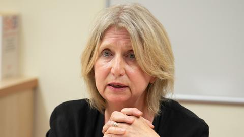 Eine blonde Frau in einem schwarzen Kostüm spricht mit ernstem Gesichtsausdruck.