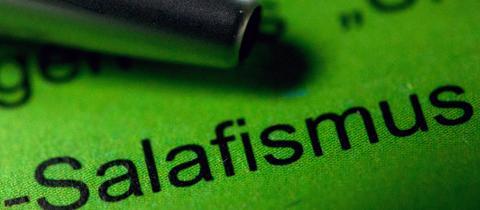 """Ein Kugelschreiber liegt auf einem Verfassungsschutzbericht neben dem Schriftzug """"Salafismus"""""""