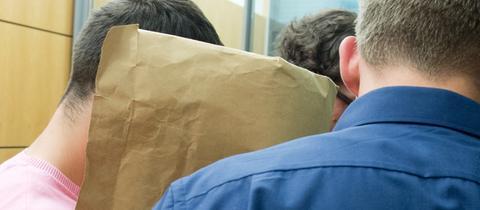 Sanel M. verbirgt während eines Proesstags sein Gesicht mit einem Umschlag