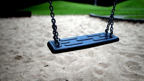 Eine leere Schaukel auf einem Spielplatz.