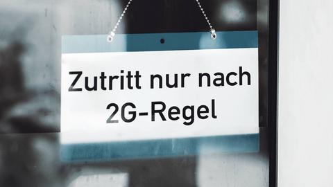 """Schild mit der Aufschrift """"Zutritt nur nach 2G-Regel"""", das an einer Glastür hängt."""