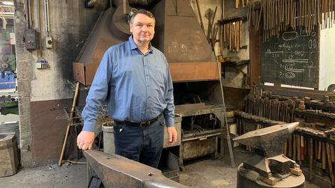Volker Scheid steht in seiner Werkstatt am Ambos
