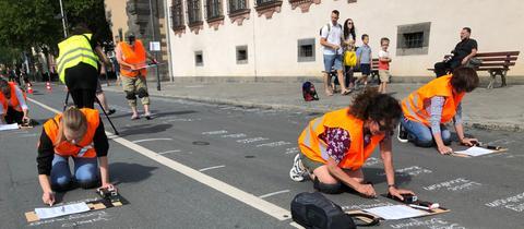 """Teilnehmer der Aktion """"Schreiben gegen das Vergessen"""" schreiben die Namen der Frankfurter Opfer des Holocausts auf die Straße"""