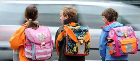 Drei Schüler warten an einer Straße in Frankfurt, auf der ein Auto vorbei fährt.