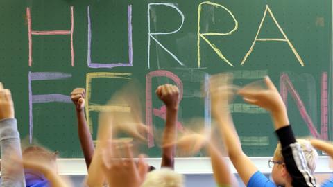 """Schultafel mit der Aufschrift """"Hurra Ferien"""" - im Vordergrund gereckte Kinderhände"""