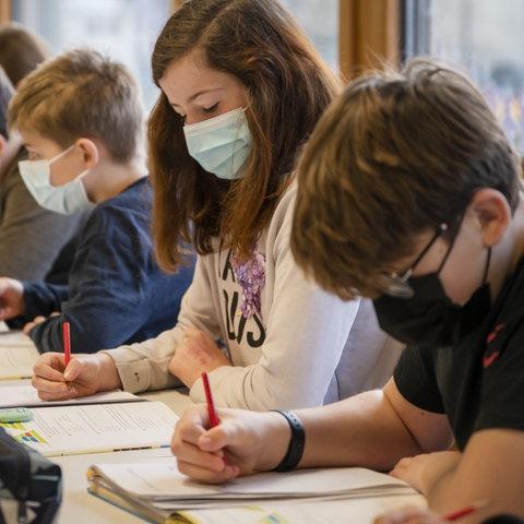 Schülerinnen und Schüler sitzen am Schreibtisch im Klassenzimmer und targen Masken.