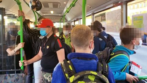 Das Foto zeigt das Innere eines Schulbusses. Viele Schüler'innen stehen dicht gedrängt.