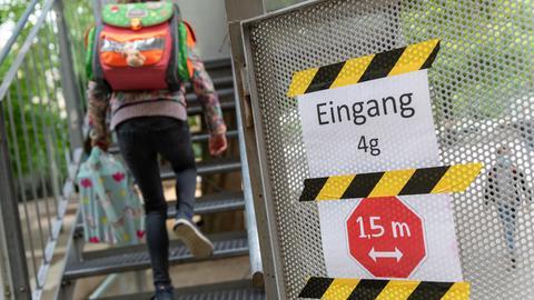 Mädchen geht Treppe hoch mit Abstandsschild