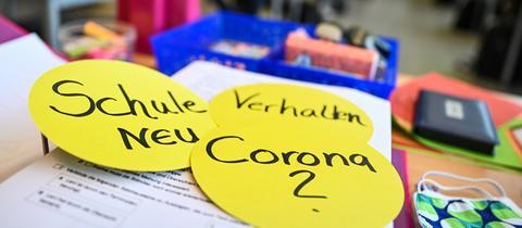 """Schreibtisch mit Büroutensilien, im Vordergrund drei gelbe, runde Workshop-Karten, beschrieben mit """"Schule neu"""", """"Verhalten"""" und """"Corona?""""."""