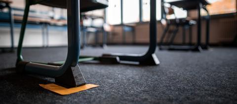 Klebestreifen auf dem Boden eines Klassenzimmers markieren die Abstandsregel